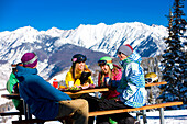 A group of snowboarders enjoy a light-hearted lunch at the top of a mountain resort., Vail, Colorado, USA