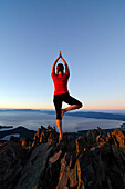 A woman performs yoga on the summit of Mount Tallac with Lake Tahoe in the background at sunset, CA., Lake Tahoe, California, USA