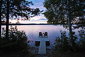 Two empty adirondack Chairs sitting on a dock on a Spencer Pond in northern Maine., Maine, USA
