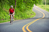 A female cyclist rides along a country road., Whately, MA, USA