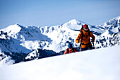 Two backcountry skiers hiking over a hill with mountains in the background., Park City, Utah, USA