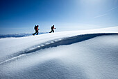 Two backcountry skiers hiking in fresh powder and bluebird skies., Park City, Utah, USA