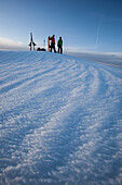 Man and woman splitboarders putting skins on in the backcountry in nice light., South Lake Tahoe, California, USA