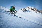 One female telemark skier making a hard turn., Ogden, Utah, USA