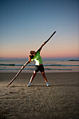 Woman doing some sport exercises on the beach at sunset., Florianopolis, Santa Catarina, Brazil