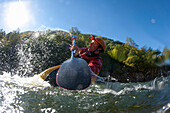 Low angle perspective of one man splashing in a kayak / playboating., Fayetteville, WV, USA