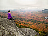 A young female hiker views vibrant fall foliage from the rocky summit of a New England peak., Elliotsville Plt., ME, USA