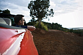 A young man looks out from the passenger seat of a red convertible sports car in Hawaii., Waimea, HI, USA