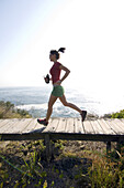 Runner on bridge along ocean trail Sydney, New South Wales, Australia
