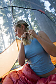 Woman braiding hair in tent Crater Lakes National Park, Oregon, United States