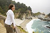 Woman crosses bridge while exploring Big Sur, California, United States