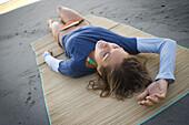 Woman lies on bamboo mat at beach Seal Beach, California, United States