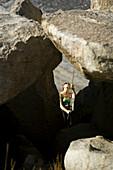 Female belaying between rocks, Bishop, California, United States