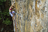 A woman climbs a rock face, Jasper, Tennessee, United States