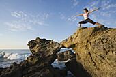 Yoga on rocky coast Malibu, California, United States
