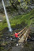 Woman runs across bridge over gorge Columbia River Gorge, Oregon, United States