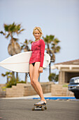 A woman in a bikini skateboards to the beach with her surfboard in hand Huntington Beach, California, United States