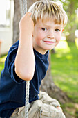 A smiling young boy swings in the backyard of his family's home on a sunny summer afternoon Costa Mesa, California, United States