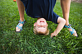 A mother holds her son upside down by his feet while he laughts in the backyard of their home Costa Mesa, California, United States