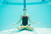 A female swimmer sits in a meditative position as seen from below the water level in an Olympic sized pool in Long Beach, Califo, Long Beach, California, United States