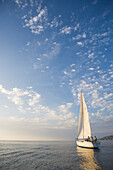 A sailing yacht out on the open water on a clear evening at sunset near San Diego, California San Diego, California, United States