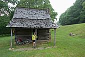 Woman standing under porch roof away from the rain while biking the Blue Ridge parkway, North Carolina Boone, North Carolina, USA