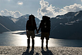 Two backpackers hold hands while overlooking a high alpine lake and distant mountains Chile