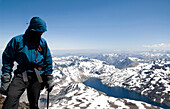 A climber stands at the summit of a peak in the Andes Mountains Chile