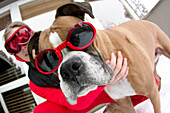 Close up of a young woman and a boxer dog wearing goggles in the snow Bend, Oregon, U.S.A.
