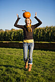 A smiling woman walks at a farm on a cool autumn afternoon while balancing a pumpkin on her head Portland, Oregon, USA