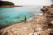 A woman walks along the coastline while on vacation Mallorca, Spain