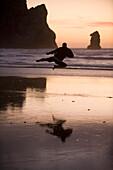 One mid adult man practices Taekwondo on the beach at sunset in Morro Bay, California Morro Bay, California, USA
