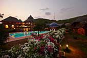 Pool, restaurant and bungalows of a hotel in the evening, Gokarna, Karnataka, India