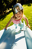 Portrait of girl climbing slide with bowl on head, Seattle, WA