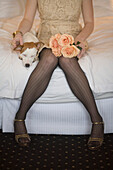 Woman in fancy dress with dog and flowers sitting on bed, Seattle, WA