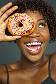 African woman holding doughnut over eye, Austin, TX