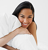 African woman hugging pillow, Unknown