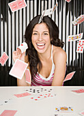 Hispanic woman throwing playing cards, Unknown