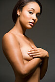 Nude Hispanic woman with arms covering breasts, Seattle, WA