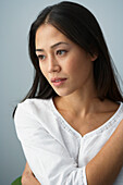 Asian woman holding arm across chest, Gaithersburg, MD