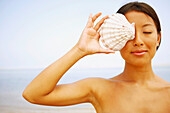 Asian woman holding seashell over eye, Cape Cod, MA