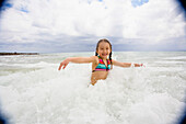 Asian girl playing in surf, Kauai, HI