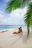 South American couple sitting on beach, Morrocoy, Venezuela