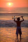 Asian boy holding surfboard at beach, Virginia Beach, VA