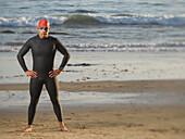 Hispanic man wearing wetsuit and goggles, Newport Beach, CA