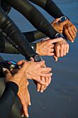 Multi-ethnic swimmers checking watches, Newport Beach, CA