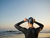 Rear view of Hispanic woman wearing wetsuit, Newport Beach, CA