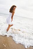 African woman standing in ocean surf, Santa Monica, CA