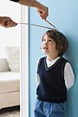 Asian boy having height measured on wall, Richmond, VA