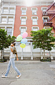African woman walking with bunch of balloons, Jersey City, NJ